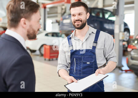 Mechanic Offering Contract to Client - Stock Photo