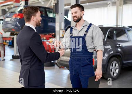 Car Mechanic Giving Keys to Businessman - Stock Photo