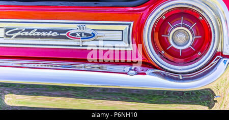 Shallow depth of field closeup of the taillight assembly and rear nameplate on a 1964 Ford Galaxie 500 XL convertible. - Stock Photo