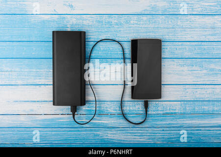 Modern Smart Phone With Drained Battery Connected To Big External Power Bank Battery Charging Concept On Blue White Wood Background Top Angle - Stock Photo