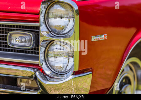 shallow depth of field closeup of the headlight assembly on a 1966 Pontiac Tempest convertible. - Stock Photo