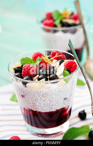 Detox and healthy superfoods breakfast in bowl. Vegan almond milk chia seeds pudding with raspberries, blackberries and  mint. - Stock Photo