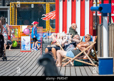 Skegness, UK. 2nd July 2018. On Skegness Pier a group of old age pensioners sit in their deck chairs and enjoy the hot weather, bright sunshine, and raising temperatures as they relax and take it easy during the current heatwave that is hiting the whole of the UK. Credit: Steven Booth/Alamy Live News. - Stock Photo