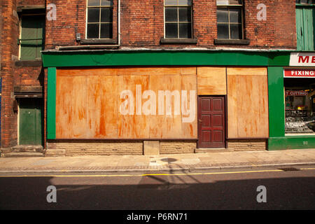 boarded up and closed up shop front in Blackburn Lancashire - Stock Photo