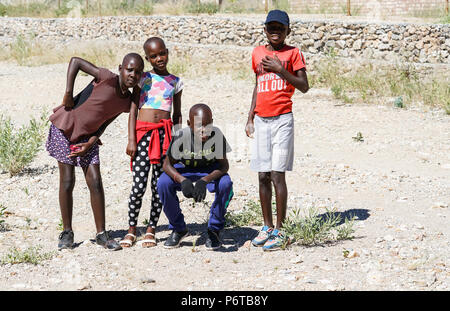 KHOHAXIS, NAMIBIA - MAY 21 2018; Four African youth two girls and two boys enjoy posing for photo - Stock Photo