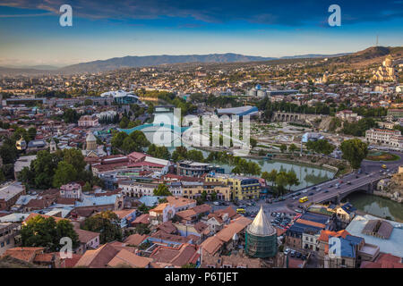 Georgia, Tbilisi, View of Tbilisi looking towards Metekhi bridge, Peace bridge and the Public Service Building, on the right - Rike Park Theater and Exhibition Hall below the Presidential Palace and Tsminda Sameba Cathedral (Holy Trinity Cathedral) - Stock Photo