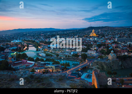 Georgia, Tbilisi, View of Tbilisi looking towards Metekhi bridge and Church, Peace bridge and the Public Service Building, on the right - Rike Park Theater and Exhibition Hall below the Presidential Palace and Tsminda Sameba Cathedral (Holy Trinity Cathedral) - Stock Photo