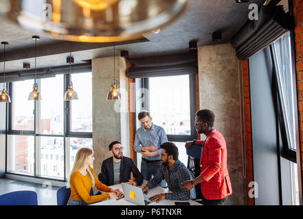 People Diversity, Teamwork, Brainstorming Togetherness Concept. Business Training Coach presenting seminar to uoung managers in modern loft office sur - Stock Photo