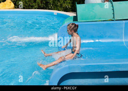 funny small thin girl on water slide in amusement park in summer sunny holiday - Stock Photo