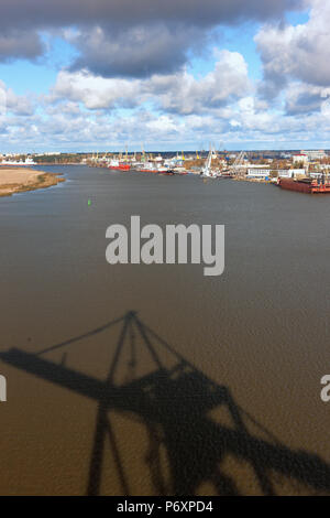Port with cranes on the Daugava River in Riga, the capital of Latvia, with a shadow on the water with waves of a crane for the loading of Containers - Stock Photo