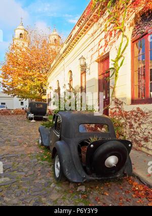 Uruguay, Colonia Department, Colonia del Sacramento, Vintage cars on the cobblestone lane of the historic quarter. - Stock Photo