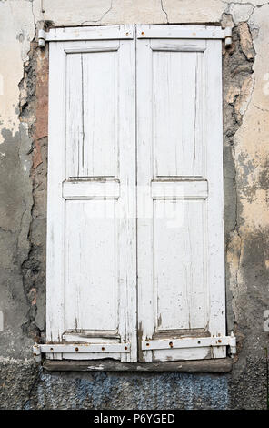 very old weathered white painted wooden doors of house in french provence - Stock Photo