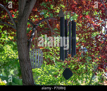 Wind chimes hanging from a tree on a colorful day - Stock Photo