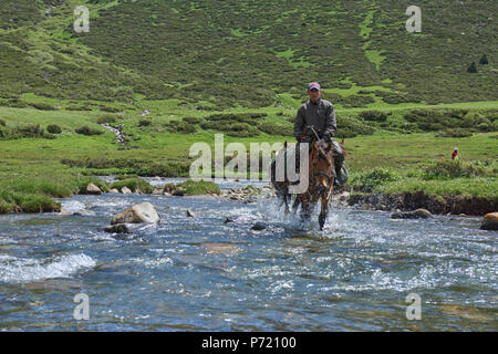 Kyrgyz horserider crossing the Tup River, Jyrgalan Valley, Kyrgyzstan - Stock Photo