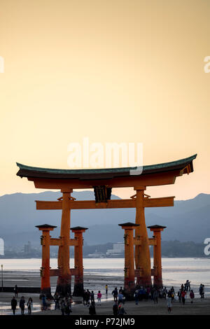 Tourists walking under the torii gate of Miyajima at low tide, Itsukushima, UNESCO World Heritage Site, Hiroshima Prefecture, Honshu, Japan, Asia - Stock Photo
