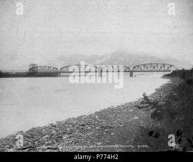 . English: Miles Glacier Bridge known as the Million Dollar Bridge, ca. 1910 . English: Construction photographs of the Copper River and Northwestern Railway along the Copper River from 1906-1911. The techniques developed by Erastus Hawkins for setting the foundations and steel work for the bridge became standards for future Arctic construction and have been studied by other engineers assigned to major Arctic engineering projects. The bridge was completed in the summer of 1910. Caption on image: E.A. Hegg 388. Miles Glacier Bridge. Copper River & Northwestern Railway, Alaska PH Coll 375.100 Su - Stock Photo