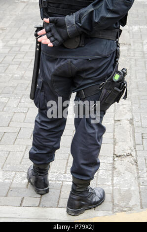 Leg of a policeman in which a firearm is found, concept of security - Stock Photo
