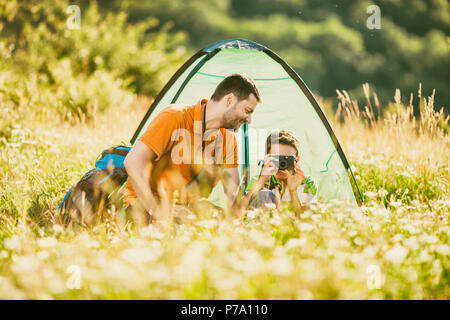 Father and son are camping in nature. Little boy is photographing. - Stock Photo