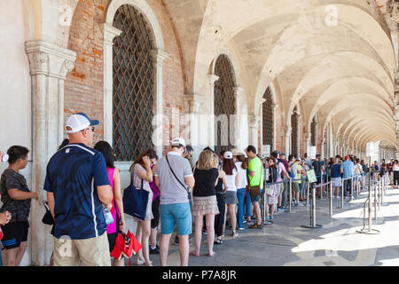 Long line of tourists queueing to enter the Doges Palace or Palazzo Ducale, San Marco, Venice, Veneto, Italy under the vaulted colonnade outside. - Stock Photo