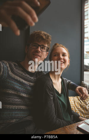 Couple taking a selfie in the cafe - Stock Photo