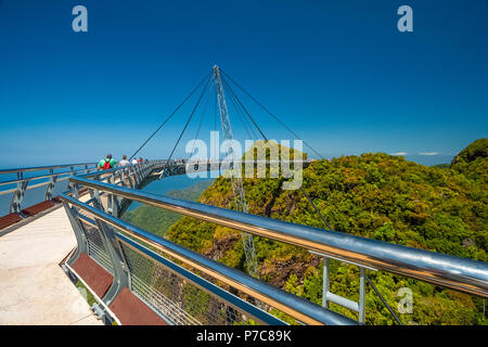 Tourists walking on the Langkawi Sky Bridge, a curved pedestrian cable-stayed bridge, suspended by cables from a single pylon, at the peak of... - Stock Photo