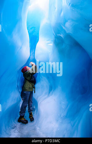 Woman photographing in a ice cave in Fox Glacier, South Island, New Zealand - Stock Photo