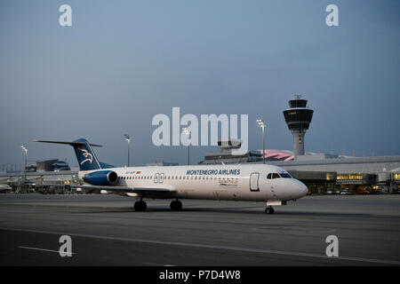 Montenegro Airlines, Fokker, F100, taxiing in front of Terminal 1 with tower, at dusk, Munich Airport, Upper Bavaria, Bavaria - Stock Photo
