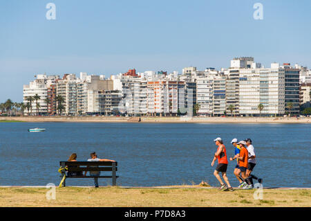 Joggers and people on a bench at the Rambla, promenade of Montevideo, Uruguay - Stock Photo