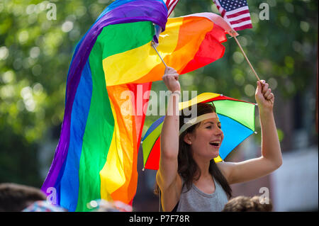 NEW YORK CITY - JUNE 25, 2017: Woman waves rainbow and US flags on the sidelines of the annual Pride Parade as it passes through Greenwich Village. - Stock Photo
