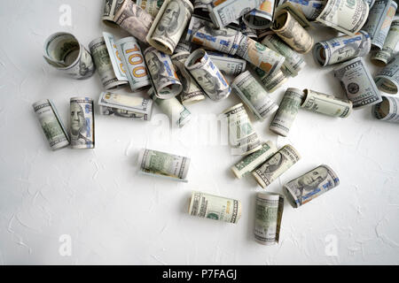 American dollar denominations of different denominations are rolled into tubes and scattered on a light surface as a symbol of a poor existence and li - Stock Photo