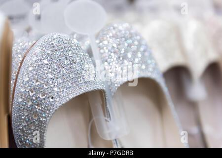 Closeup of many shining ballet flat style flats shoes embellished with crystals, pearls, embellishments on retail display in wedding store, shop, shop - Stock Photo