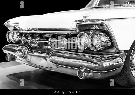 Chrysler Imperial Crown 1959 in black and white. Selective focus on the right headlights. Isolated on black background - Stock Photo
