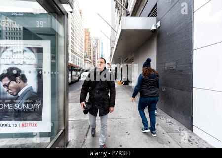New York City, USA - April 7, 2018: Manhattan NYC midtown Herald Square, 6th avenue road, happy person man people pedestrians walking, photographer wi - Stock Photo