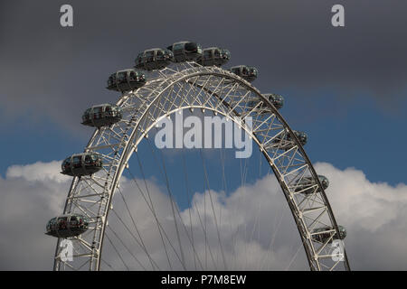 Top half of the London Eye Ferris wheel against a blue sky with shite and gray clouds, shining in the sunlight, steel bracing and tensioned cables. - Stock Photo
