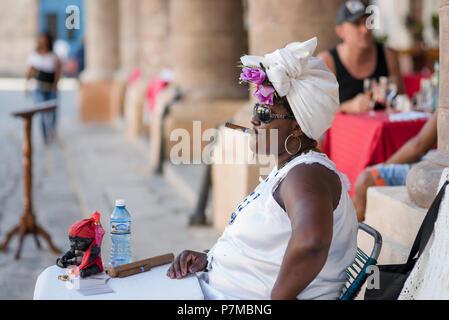 Theresa the fortune teller smoking a Cuban cigar and enjoying the the beautiful weather in Plaza de la Catedral, Havana, Cuba. - Stock Photo