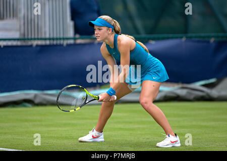 A professional tennis player (Katie Swan) positioned in the ready position during a match. Swan is awaiting a serve from her opponent. - Stock Photo