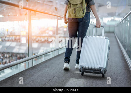 Close up lower body of woman traveler with luggage suitcase going to around the world by plane. Female tourist on automatic escalator in airport termi - Stock Photo