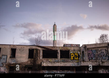 Minaret of the mosque behind the building damaged by artillery shelling of the Bosnian Civil War, Sarajevo, Bosnia and Herzegovina - Stock Photo