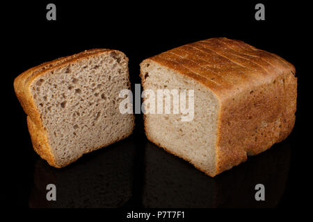 Ordinary bread cut into pieces on a black background - Stock Photo