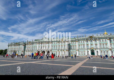 Tourists sightseeing at the Winter Palace from the Palace Square in St Petersburg - Stock Photo