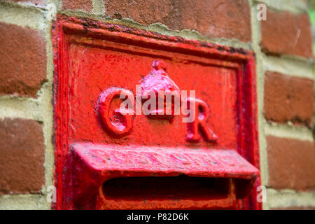 Royal cypher on a red English post box from the time of King George V, Lewes, UK - Stock Photo