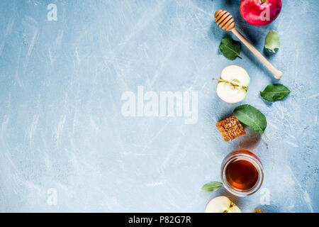 Jewish holiday Rosh Hashanah or apple feast day concept, with red apples, apple leaves and honey in jar, light blue background copy space above - Stock Photo