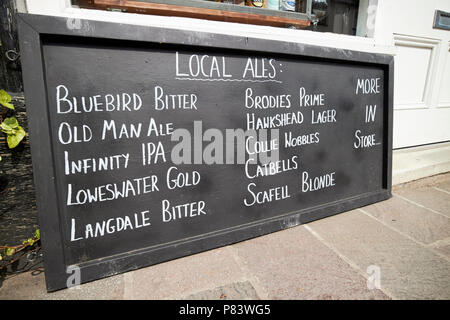 handwritten sign for local ales outside a small off licence windermere lake district cumbria england uk - Stock Photo