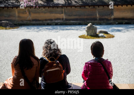 Japanese tourists enjoy tranquility at Ryoanji Temple in Kyoto, Japan. This Zen Buddhist temple is famous for its rock garden. - Stock Photo
