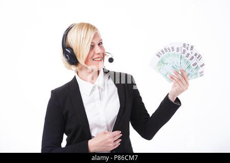 Happy smiling call center operator, blonde woman dressed in black jacket holding stack of euro banknotes before white background with copyspace - Stock Photo