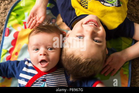 SMILING HAPPY BROTHERS 3 MONTH OLD BABY BOY AND 3 YEAR OLD BOY - Stock Photo