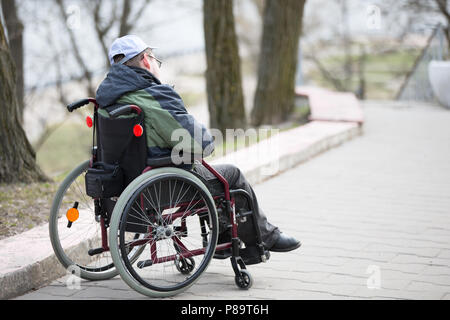 Belarus, Gomel, on April 11, 2018. City Day. Central Park.A man in the street in a wheelchair - Stock Photo