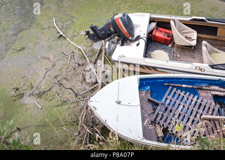 View looking down on two small boats at low tide and during the dry weather, July 2018 in the UK. - Stock Photo