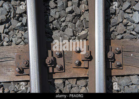Rails on the wooden sleepers with basalt stone as a substructure. - Stock Photo