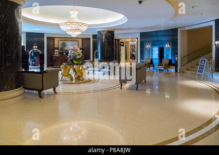 Large spacious hall with sofas, columns and decorative flowers on the table . For your design - Stock Photo